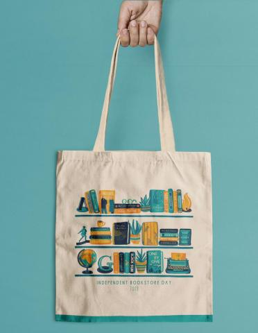 a hand holding a canvas Independent Bookstore Day 2021 tote bag featuring Simon & Schuster titles in blue and yellow