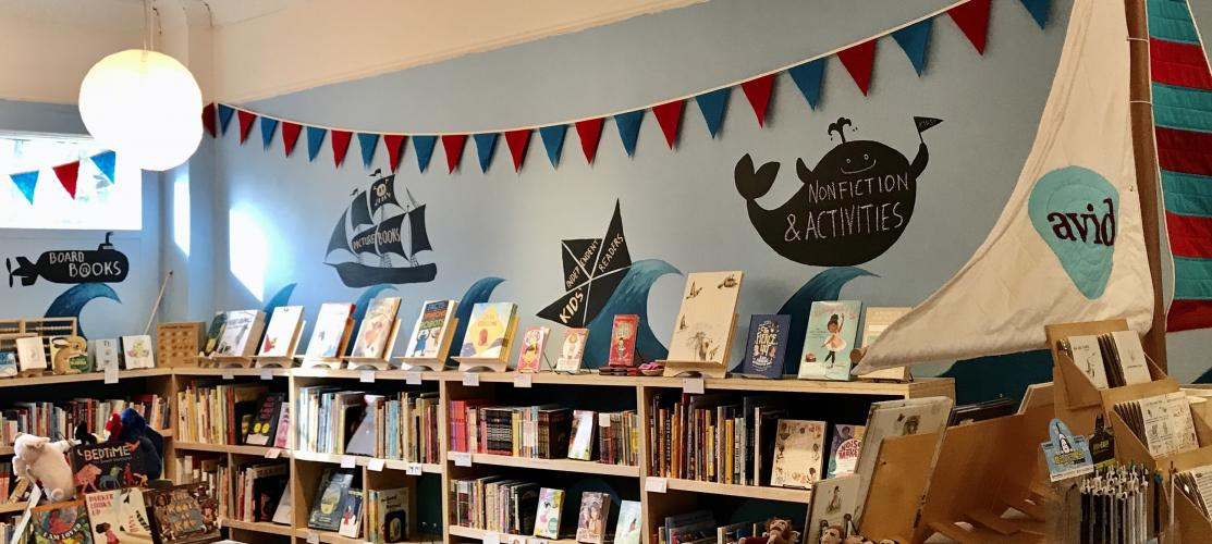 Avid Bookshop kids' section with bunting, book boat sail, and section signs